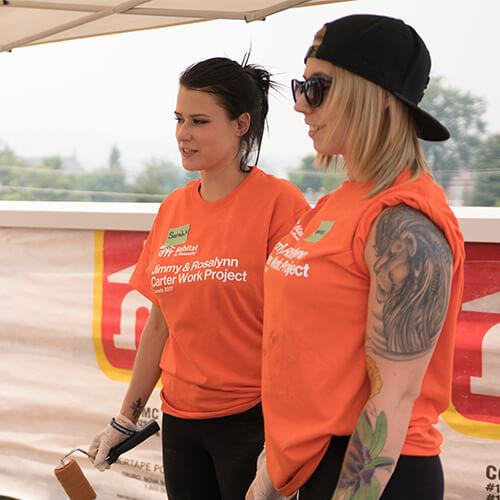 Two volunteers painting baseboards